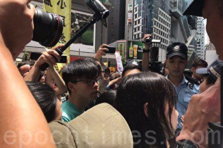 港眾志在銅鑼灣地鐵站出口派發傳單時,被警方阻撓。(林怡/大紀元)