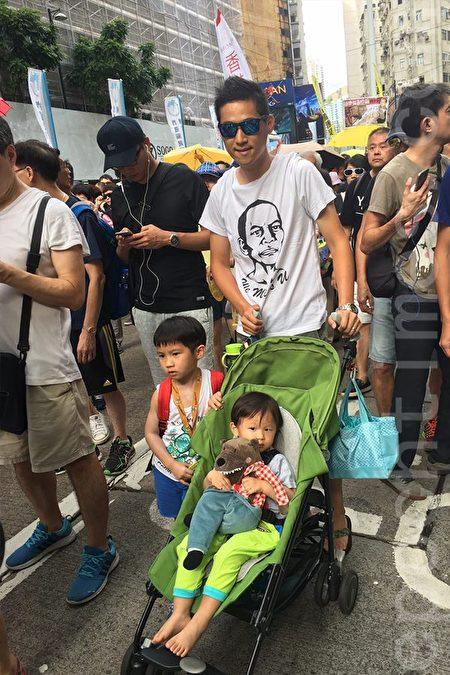 從事工程行業的黎先生夫婦帶同2歲和6歲孩子上街,大的背著小背囊,小的還坐著嬰兒車。(黃瑞秋/大紀元)