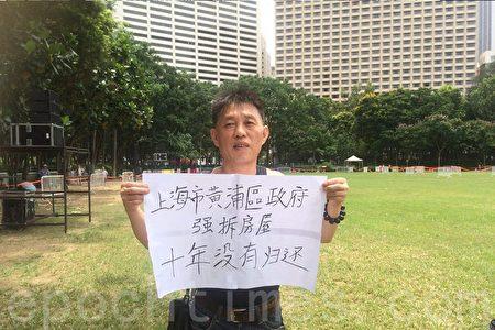 來自上海的李先生來港參加七一遊行。他拿著一幅「上海市黃浦區政府 強拆房屋 十年沒有歸還」標語表達訴求。(梁珍/大紀元)