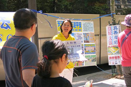 孙女士在法国向中国大陆游客讲述法轮功真相。(关宇宁/大纪元)