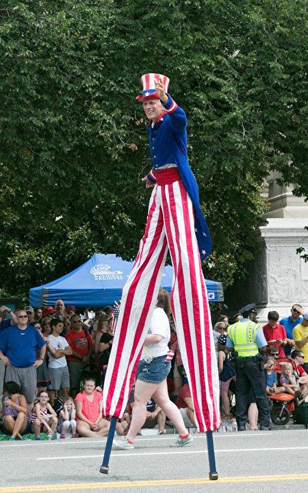 2017年華府國家獨立日大遊行。身穿紅白藍色服裝的表演者在踩高蹺。(李莎/大紀元)