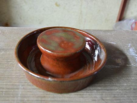 桌腳墊(菜櫥腳)就是墊在餐桌或菜櫥四個桌腳下的圓陶墊,有特製一圈凹槽來盛水,可防螞蟻。(鄧玫玲/大紀元)