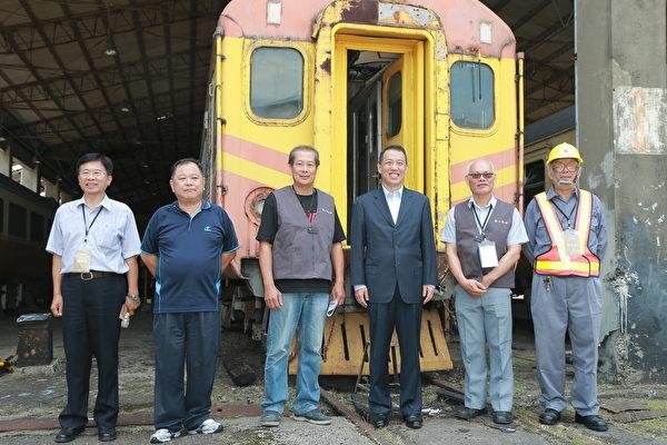 文化部次長楊子葆、導覽志工於客車工場前,與第一代自強號EMU-100英國貴婦號合影。(文化部/提供)