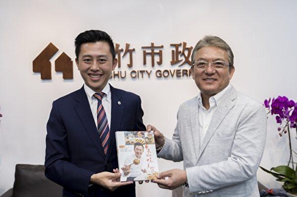 林智坚(左)赠与小出让治市长(右)美食书。(新竹市府提供)