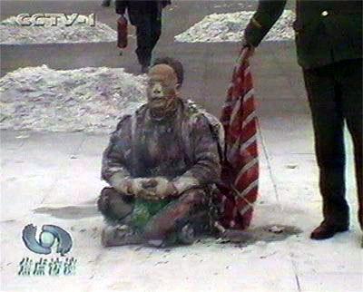 """天安门自焚伪案中自焚时的王进东。警察拿着所谓的""""防火毯"""",却垂在王进东的身后,垂在下面,是在做戏,不是在救""""火""""。(网络图片)"""
