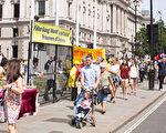 7月18日,部分英国法轮功学员在议会大厦外手持标语,展示功法,为来往行人分发真相传单。(肖龙/大纪元)