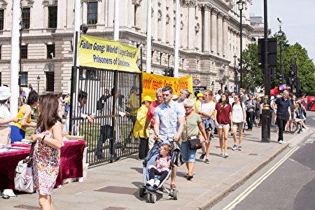7月18日,部分英國法輪功學員在議會大廈外手持標語,展示功法,為來往行人分發真相傳單。(肖龍/大紀元)