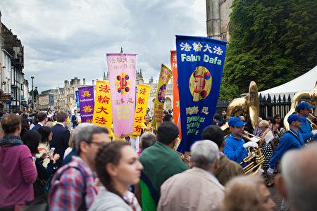 欧洲天国乐团和英国法轮功学员的游行队伍穿过剑桥游人最稠密的景点,人们都被雄壮的鼓乐声和色彩鲜亮的法轮大法横幅吸引,驻足观看。(Laphare/大纪元)