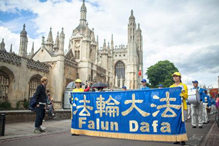 由法輪大法學員組成的遊行隊伍穿行於劍橋大學著名景點,不少遊人駐足觀看。(Laphare/大紀元)
