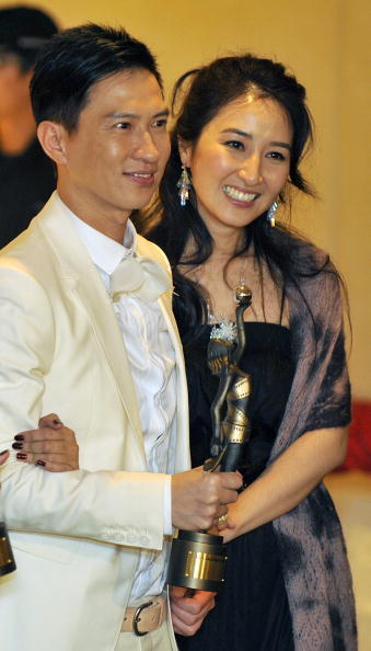 """HONG KONG - APRIL 19: Hong Kong actor Nick Cheung (L) poses with his wife actress Esther Kwan after winning the Best Actor award for his role in """"The Beast Stalker"""" during the 28th Hong Kong Film Awards 2009 at the InterContinental Hong Kong hotel on April 19, 2009 in Hong Kong. (Photo by Victor Fraile/Getty Images)"""