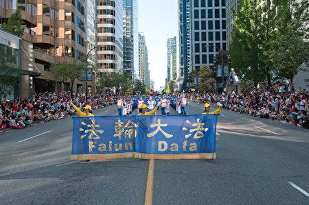 圖說:溫哥華150週年國慶大遊行中,法輪大法的遊行隊伍讓觀眾倍感親切。(攝影:大宇/大紀元)