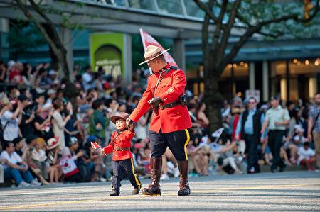 圖說:一名小「騎警」邁著小步,也要跟上旁邊騎警叔叔的步伐,為國慶楊威。(攝影:大宇/大紀元)