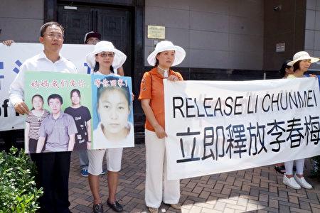 与李春梅一家相识十多年的刘晓斌夫妇手举好友一家照片,要求中共立即释放李春梅。(易永琦/大纪元)