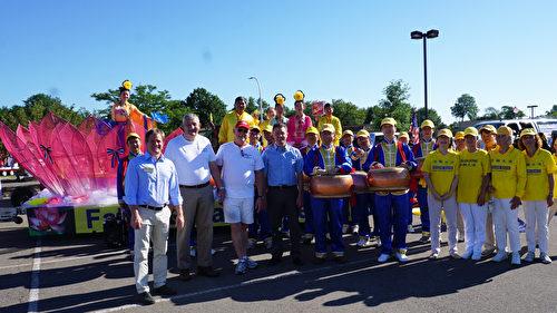 图:游行开始前,密西根州第13区的州参议员Marty Knollenbery(前排,左一),第41区的州议员Martin Howrylak(前排,左四)和Howrylak的助理Ray Watts(前排,左二)驻足法轮功学员的花车旁与参加游行的部分法轮功们合影。(林慧心/大纪元)