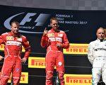 F1匈牙利站,法拉利车手维特尔(中)获得冠军,其队友莱科宁(左)获得第二名,奔驰车手博塔斯(右)位居第三。(ATTILA KISBENEDEK/AFP/Getty Images)