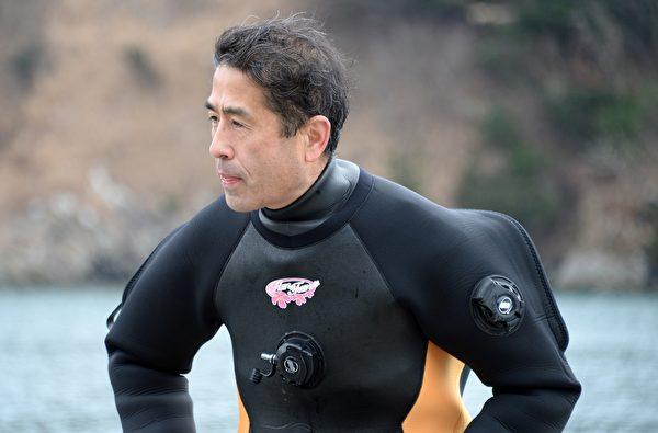 妻子的可能离世,一度击垮高松康夫。图为2014年3月2日,57周岁的康夫下海寻找海啸中失踪的妻子。(TORU YAMANAKA/AFP/Getty Images)