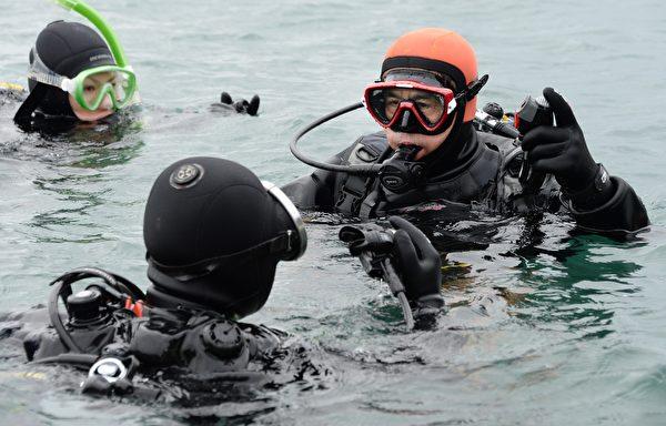 不顾自己的年龄,高松康夫仍努力学习潜水,下海寻妻。图为2014年3月2日,57周岁的康夫下海寻找海啸中失踪的妻子。(TORU YAMANAKA/AFP/Getty Images)