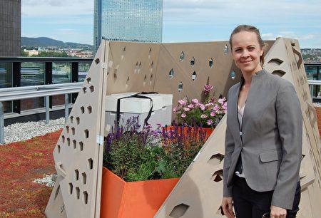 """挪威奥斯陆的会计师、业余养蜂人Marie Skjelbred展示她的蜂巢,这个看起来很酷的蜂巢属于""""蜜蜂高速公路""""项目,这里面生活着4.5万只工蜂。此图摄于2015年。(Pierre-Henry DESHAYES/AFP/Getty Images)"""