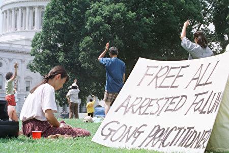 """1999年7月27日,部分美国法轮功学员在国会前炼功,手写标语""""释放所有被捕法轮功学员""""。(Alex Wong/Getty Images)"""