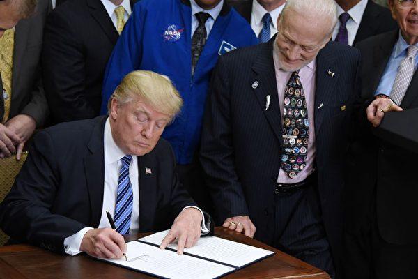 美国总统川普6月30日签署行政令,重建国家航天委员会。阿波罗11号登月宇航员布兹·奥尔德林(Buzz Aldrin)(右)在一旁见证川普的签署。(Olivier Douliery-Pool/Getty Images)