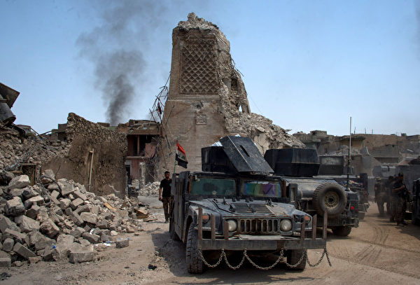 "TOPSHOT - Iraqi Counter-Terrorism Service (CTS) stand guard next to Mosul's destroyed ancient leaning minaret, known as the ""Hadba"" (Hunchback), in the Old City of Mosul on July 4, 2017, during the ongoing offensive to retake the city from Islamic State (IS) group fighters. / AFP PHOTO / Fadel SENNA (Photo credit should read FADEL SENNA/AFP/Getty Images)"