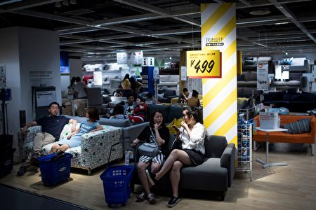 This picture taken on July 5, 2017 shows people escaping the summer heat by relaxing on a sofa in a Ikea store in downtown Shanghai. According to a local news paper Shanghai Meteorological Bureau recorded a temperature high of high of 36.2 degrees Celsius during that time. / AFP PHOTO / Johannes EISELE (Photo credit should read JOHANNES EISELE/AFP/Getty Images)