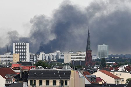 Dark smoke hangs over the Schanzenviertel district on July 7, 2017 in Hamburg, northern Germany, where leaders of the world's top economies gather for a G20 summit. Protesters clashed with police and torched patrol cars in fresh violence ahead of the G20 summit, police said. German police and protestors had clashed already on Thursday (July 6, 2017) at an anti-G20 march, with police using water cannon and tear gas to clear a hardcore of masked anti-capitalist demonstrators, AFP reporters said. / AFP PHOTO / DPA / Boris Roessler / Germany OUT (Photo credit should read BORIS ROESSLER/AFP/Getty Images)