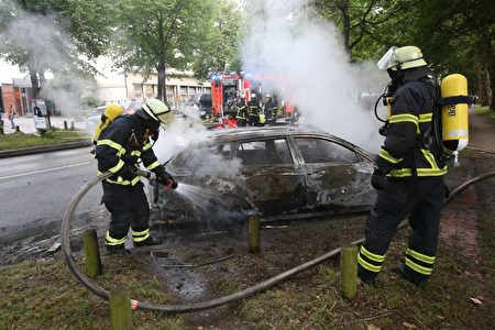 7月7日G20會議期間,德國漢堡發生了嚴重的抗議活動,大約10萬人參加示威。圖為警方在澆滅燃燒的警車。(BODO MARKS/AFP/Getty Images)