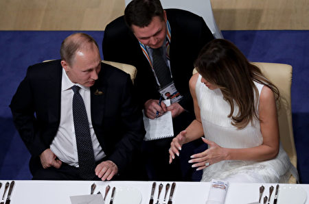 週五(7月7日)的G20晚宴上,梅拉尼婭跟普京交談愉快。(KAY NIETFELD/AFP/Getty Images)