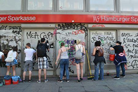7月9日(週日),在漢堡G20峰會過後,善澤區街頭出現了許多志願者,收拾當地被極端暴力份子打砸搶後留下的殘局,其中不少是年輕人。(CHRISTOF STACHE/AFP/Getty Images)