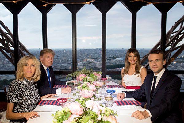 2017年7月13日,法国巴黎,法国总统马克龙(右前)和妻子布丽吉特(左前)宴请美国总统川普(左后)和其夫人梅拉尼娅(右后)在艾菲尔铁塔上的顶级餐厅享用米其林等级的法式美食。(SAUL LOEB/AFP/Getty Images)