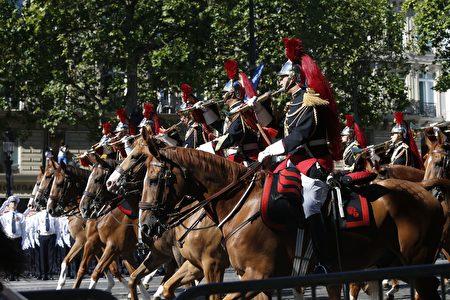 法國騎兵儀仗隊跟隨在總統的座車後面,行進在香榭麗舍大道上。 (GEOFFROY VAN DER HASSELT/AFP/Getty Images)