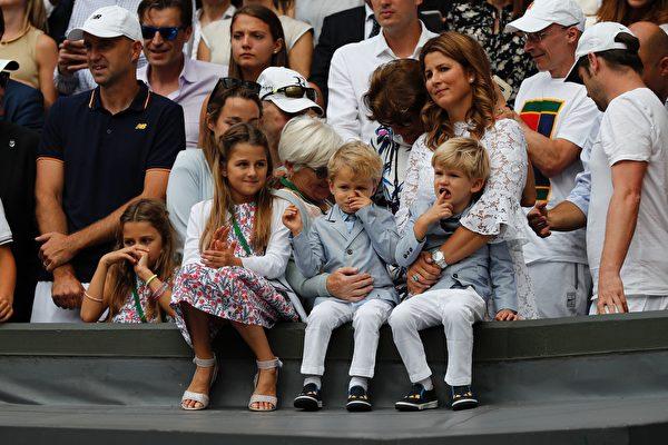 瑞士网球名将费德勒妻子(图右抱小孩者)带着两对双胞胎在场边观赛颁奖典礼。(ADRIAN DENNIS/AFP/Getty Images)