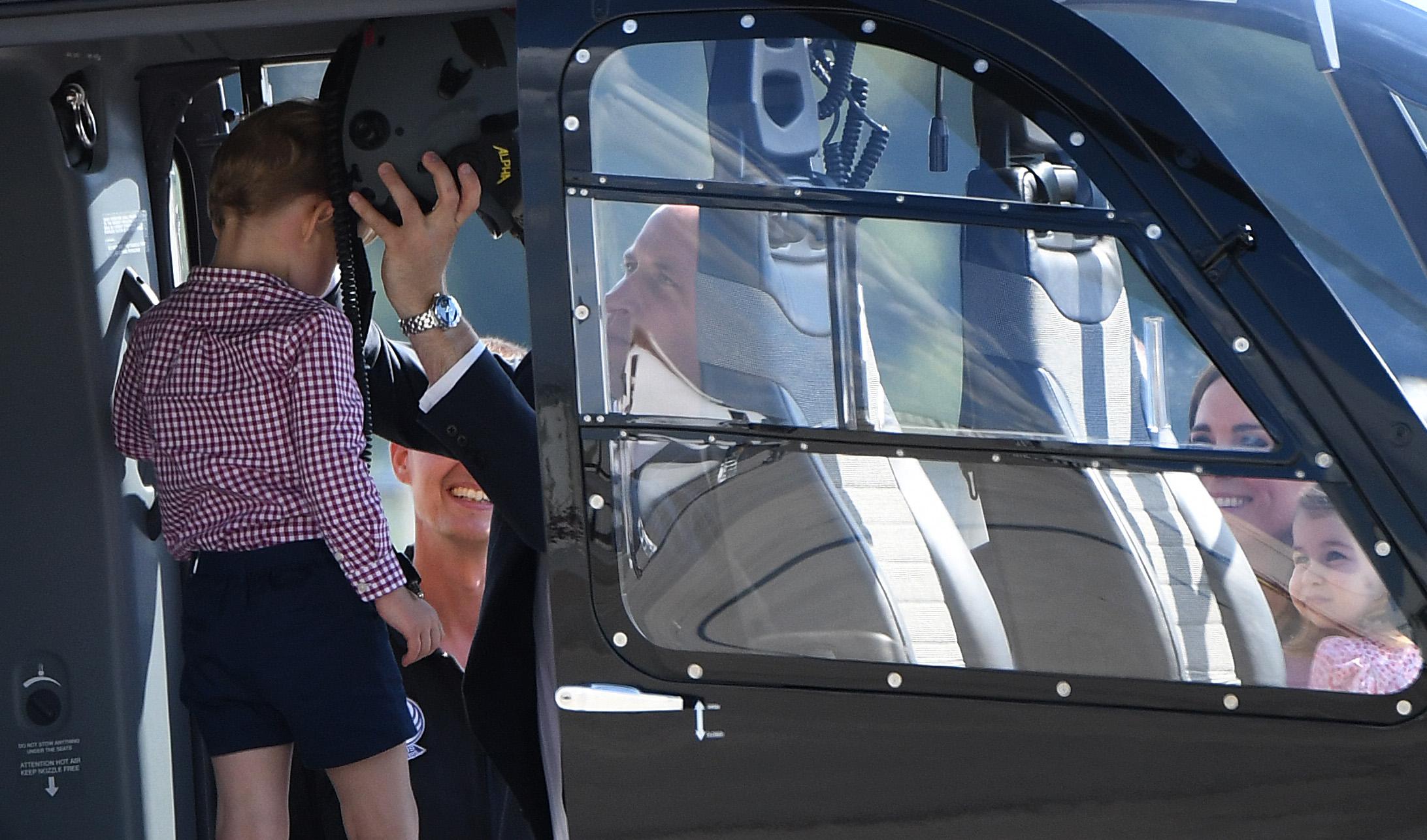 2017年7月21日,英国威廉王子携妻子与一对子女在德国汉堡参观一架直升机,威廉王子帮即将满4岁的乔治王子戴上头盔。(PATRIK STOLLARZ/AFP/Getty Images)