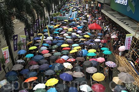 七一遊行隊伍在雨中撐起傘繼續前行。(孫青天/大紀元)