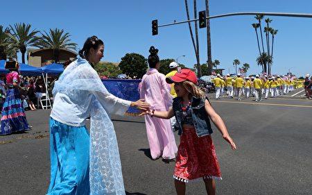 观看国庆游行的小女孩与身穿汉服的法轮大法学员击掌互动。(徐绣惠/大纪元)