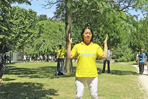 孙女士在埃菲尔铁塔下的战神广场上炼功。(关宇宁/大纪元)