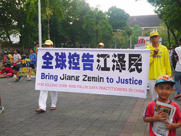 巴厘島法輪功學員反迫害遊行。圖中是法輪功學員打出全球控告江澤民。(蕭律生/大紀元)