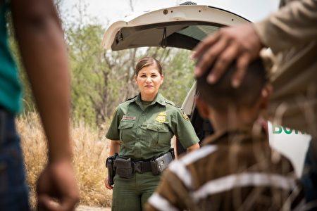 边界巡逻队一名员工马琳•卡斯特罗(中)与一群非法移民谈话,这些非法移民在2017年5月26日从墨西哥越境到德州。(Benjamin Chasteen/大纪元)