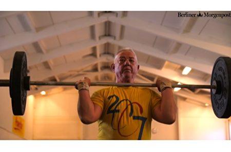 沃尔夫冈·萨多斯基(Wolfgang Sadowski )为参加8月的欧洲杯老年举重比赛做着准备。(视频截图,脸书图片/大纪元合成)