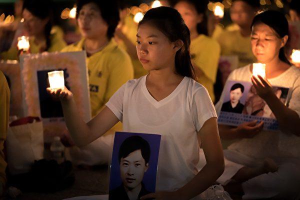 来自辽宁的女孩徐鑫洋手捧父亲徐大为的遗像。徐大为因为坚持修炼法轮功被原判监禁8年,出狱后13天离世。(石青云/大纪元)