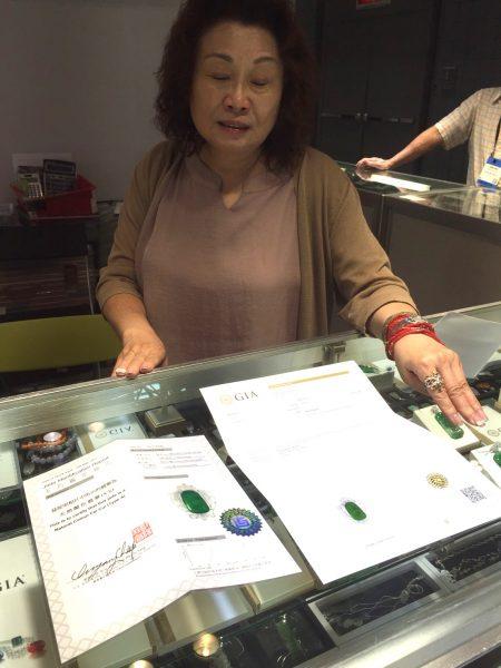 Lings首饰店老板陈龄给客人展示他们产品的GIA证书。