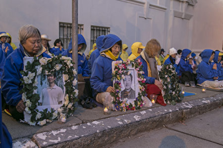 韓淑華(左1)手裡拿著兒子葉浩的遺像,靜靜地坐在舊金山中領館前。(曹景哲/大紀元)
