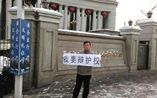 圖為建三江法輪功案律師張維玉在黑龍江人大門前舉牌要求律師辯護權。(大紀元資料室)