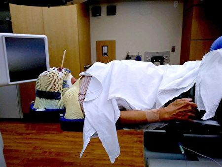 患者戴上特別製作的頭帽、接受放射治療10~15分鐘。(周梅麥拉提供)