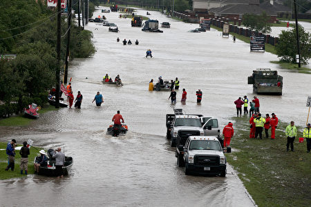 HOUSTON, TX - AUGUST 29: People make their way out of a flooded neighborhood after it was inundated with rain water following Hurricane Harvey on August 29, 2017 in Houston, Texas. Harvey, which made landfall north of Corpus Christi August 25, has dumped nearly 50 inches of rain in and around Houston. (Photo by Scott Olson/Getty Images)