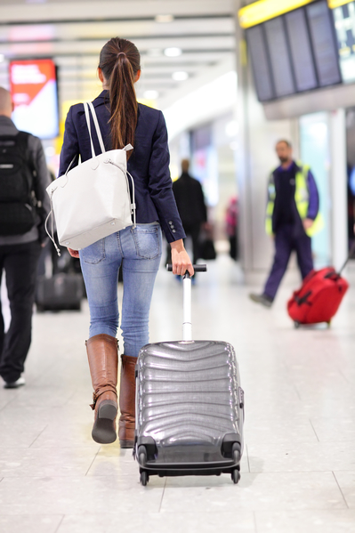 Travel woman walking in an airport with a luggage baggage carry-on trolley in full body length. Young female traveler at international airport gate going traveling.(fotolia)