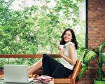 自信的年轻亚裔女人在智能休闲服装,坐在咖啡杯,坐在创意办公室或咖啡馆附近的窗口。(Fotolia)