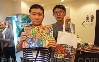 自閉症畫家高進宇(左)將自己的美麗畫作,轉製成商品提袋。(李怡欣/大紀元)