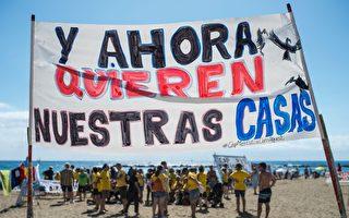 2017年8月12日,巴塞隆納沿海區巴塞羅內塔居民抗議的布條上寫著:「我們不希望旅客進到我們的建築物來。」(JOSEP LAGO/AFP/Getty Images)